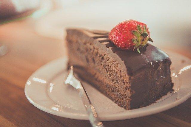 torta-sacher-nel-piattino-con-forchetta-accanto-e-fragola-sopra